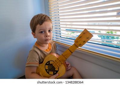 happy boy with a guitar near the window