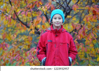 The  happy boy in hat outdoors in autumn city park