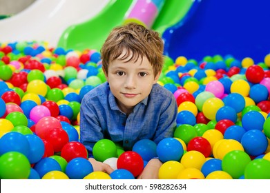 Happy boy having fun in ball pit on birthday party in kids amusement park and indoor play center. Child playing with colorful balls in playground ball pool. Activity toys for little kid