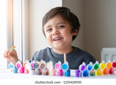 Happy boy having fun painting water colour on paper,Kid holding art brush learning painting and drawing at home,Indoor activities for children on cold weather on winter,Art for kids concept