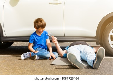Happy boy helping his father repairing car outside
