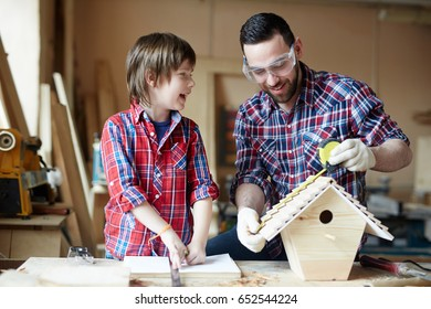 Happy boy helping his father in workshop while he measuring roof of starling-house