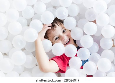 happy boy hiding under white balls at the playground