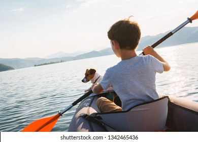 Happy boy with his dog Jack Russell Terrier paddling an inflatable kayak on the water mountain lake against the backdrop of beautiful orange sunset. Family sports vacation. Lens flare. Pet