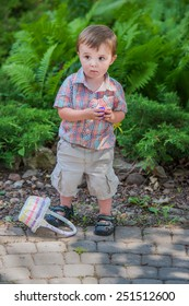 A happy boy with his Easter basket on the ground holds a purple Easter egg he finds during an Easter egg hunt activity in the spring season in a beautiful garden setting.