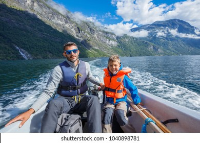 Happy boy with his father driving the motorboat, Geirangerfjord, Norway. They are enjoying the moment.