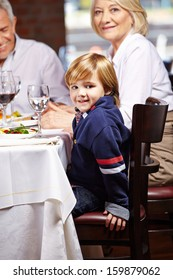 Happy boy with his grandparents eating out in a restaurant