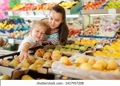 Happy boy with his mother choosing fresh pears and apples at fruit department of supermarket