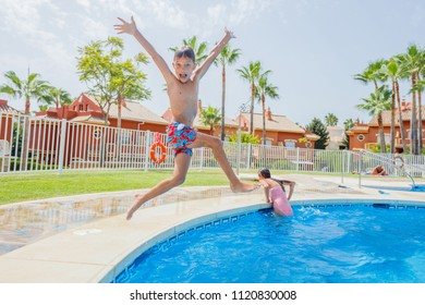 Happy boy with his sister jumping in the pool