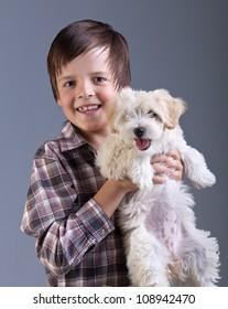 Happy boy holding his fluffy dog - best childhood friend