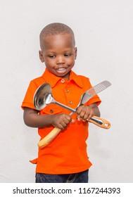 Happy boy holding kitchen wares