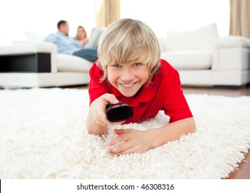 Happy boy holding a remote lying on the floor in the living-room