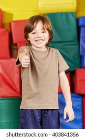 Happy boy holding thumbs up in gym of kindergarten