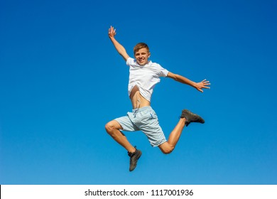 happy boy jumping in the blue sky , concept of happiness