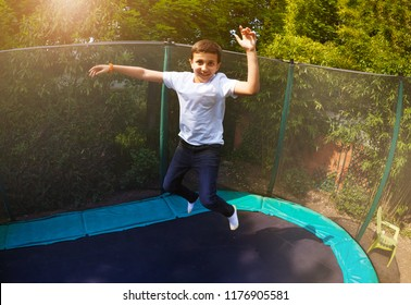 Happy boy jumping high on the backyard trampoline