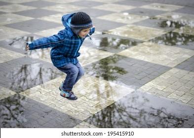 Happy boy jumping on a big chessboard