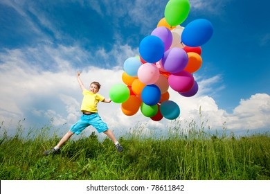 Happy boy jumpy on meadow with balloons