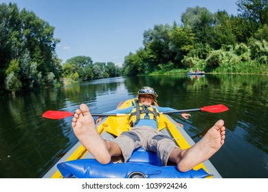 Happy boy kayaking on the river. Active boy having fun enjoying adventurous experience with kayak on a sunny day during summer vacation
