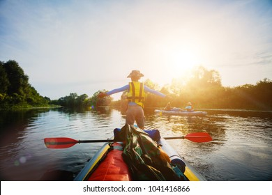 Happy boy kayaking on the river. Active boy having fun enjoying adventurous experience with kayak On the Sunset during summer vacation