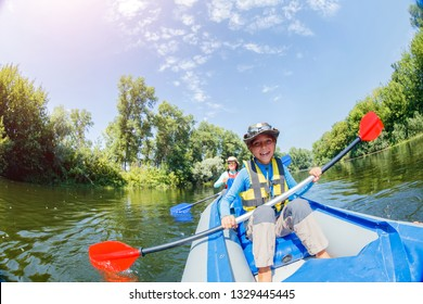 Happy boy kayaking on the river. Active boy with his sister having fun and enjoying adventurous experience with kayak on a sunny day during summer vacation