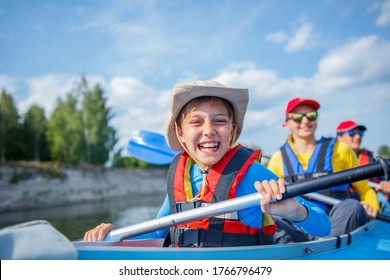 Happy boy kayaking on the river. Active boy with his sisters having fun and enjoying adventurous experience with kayak on a sunny day during summer vacation