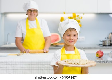 Happy boy in the kitchen holds a cooked dumplings in his hands, grandmother in the background