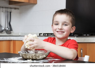 happy boy kneading dough with hands in the kitchen