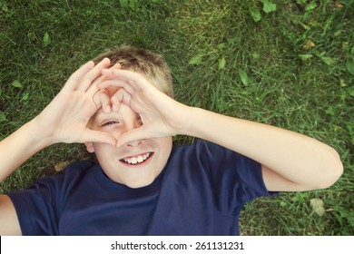 Happy boy laying outdoors making a heart shape with his hands.