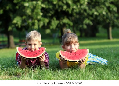 happy boy and little girl with watermelon lying on grass