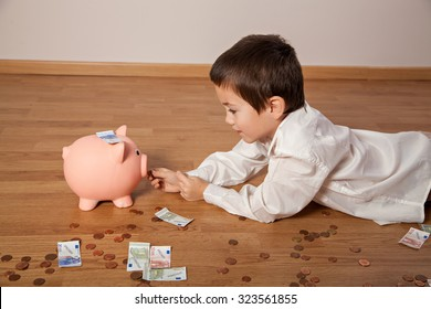 Happy boy lying on the floor with money and a piggy bank