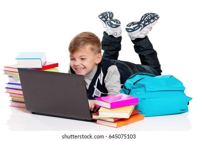 Happy boy lying on floor with laptop and books isolated on white background