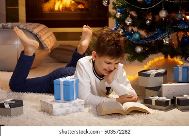 Happy boy lying on front on floor by christmas tree, reading book surrounded by gifts.