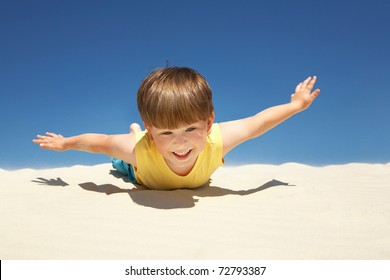 Happy boy lying on sand with outstretched arms on beach