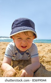 Happy boy lying in the sand on a beach wearing a sun hat