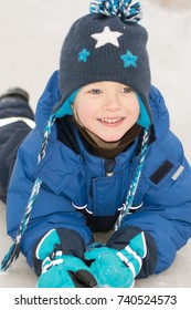 Happy boy lying in a snow - winter leisure for children