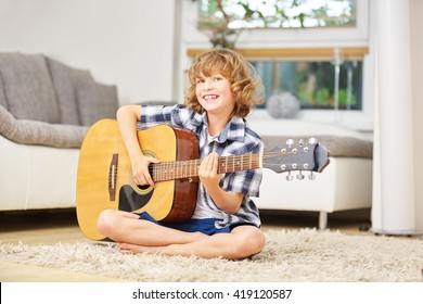 Happy boy making music playing the guitar at home
