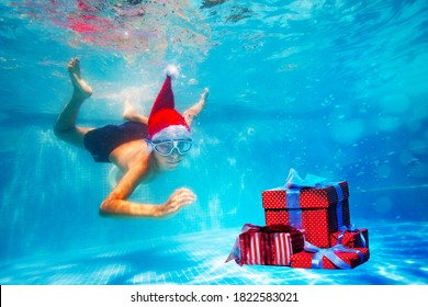 Happy boy in mask dive underwater in Santa Claus hat in the pool reaching for Christmas presents boxes on New Year vacation