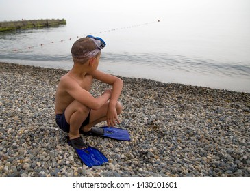 happy boy in mask and flippers standing on the pebble beach, getting ready to dive