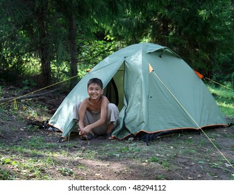 happy boy near camping tent in summer forest