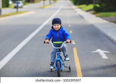 Happy boy on a bicycle at asphalt road. Cute boy learning to ride bicycle on a bicycle track. Adorable boy having fun on his first bicycle. Boy loves bike sport. Conceptual picture of boys world.
