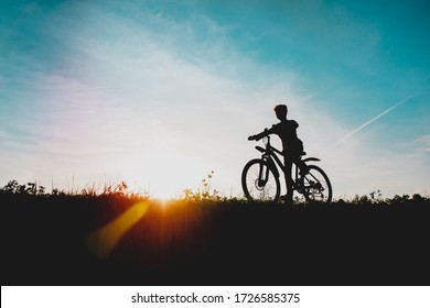 happy boy on bike ride in sunset nature