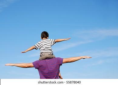 Happy boy on mans shoulders