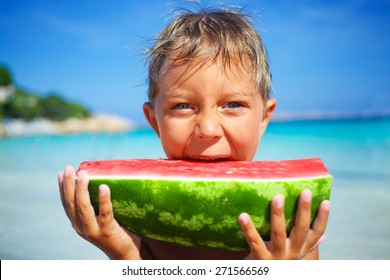 Happy boy on the sea with watermelon