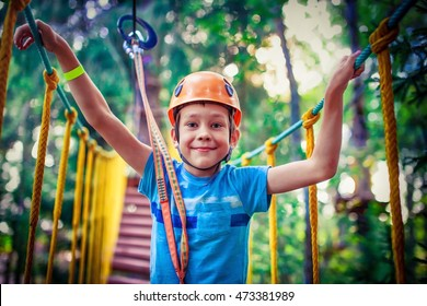 happy boy on the zip line. proud of his courage the child in the high wire park. HDR