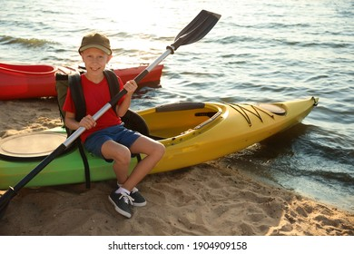 Happy boy with paddle sitting on kayak near river. Summer camp activity