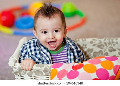 Happy boy in a plaid shirt basket with toys