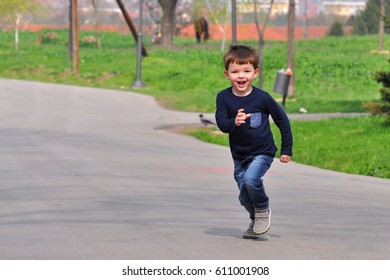 Happy boy play and running at park in spring. Little smiling kid play in city park.