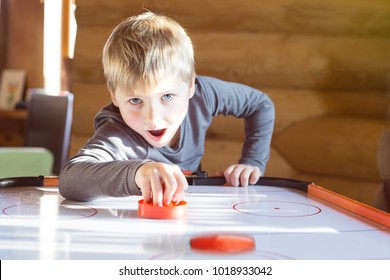 Happy boy playing air hockey with passion at home.