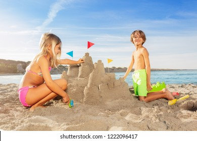 Happy boy playing beach games with his sister