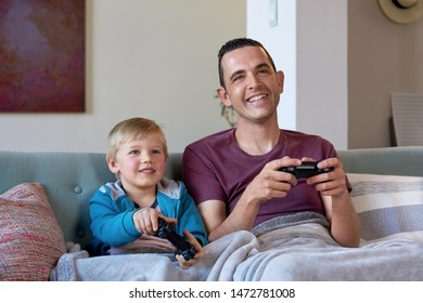 Happy boy playing computer games with his dad at home, racing cars close relationship between father child